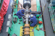 Overhead view of engineers inspecting gears on generator in turbine hall of nuclear power station during outage - CUF47957