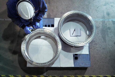 Overhead view of engineer measuring oil seals in nuclear power station during outage - CUF47960