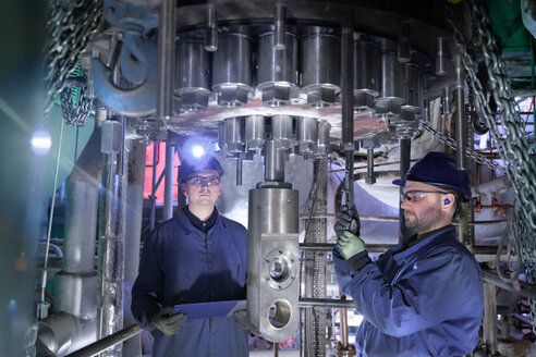 Engineers working in confined space under turbine during outage in nuclear power station - CUF47966