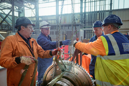 Engineers craning large gear into place in turbine hall of nuclear power station - CUF47972