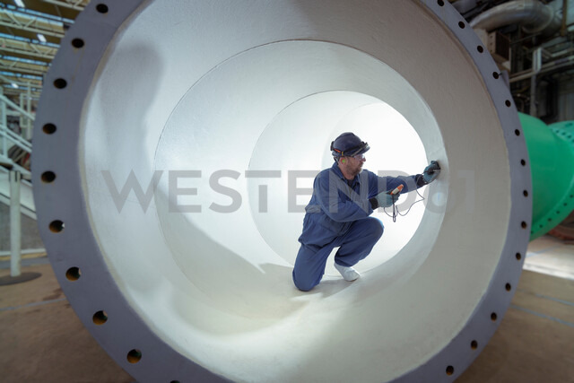 Testing protective paint in large pipe in turbine hall of nuclear power station - CUF47975