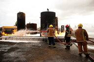 Firemen training, spraying firefighting foam onto oil storage tank fire at training facility - CUF47981