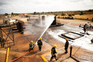 Firemen training, firemen spraying firefighting foam at oil storage tank at training facility - CUF47984