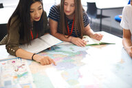 College students studying world map in classroom - CUF48014