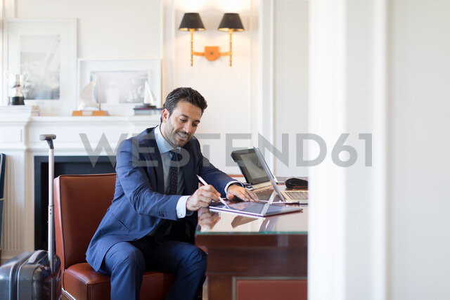 Businessman writing on digital tablet in office - CUF48053