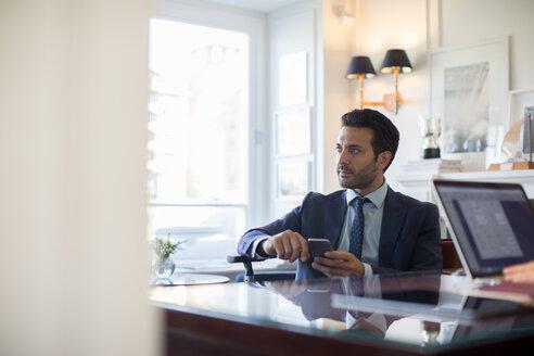 Businessman using smartphone in office - CUF48056