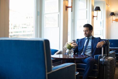 Businessman using smartphone in office - CUF48059