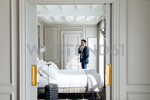 Businessman using smartphone in suite - CUF48074