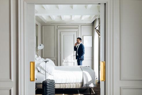 Businessman using smartphone in suite - CUF48074