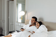 Couple laughing and relaxing in suite - CUF48080