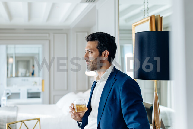 Businessman with iced drink, deep in thoughts in suite - CUF48083