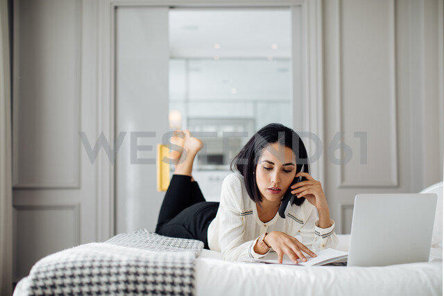 Businesswoman using smartphone and laptop in suite - CUF48089 - Sofie Delauw/Westend61