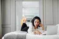Businesswoman using smartphone and laptop in suite - CUF48089