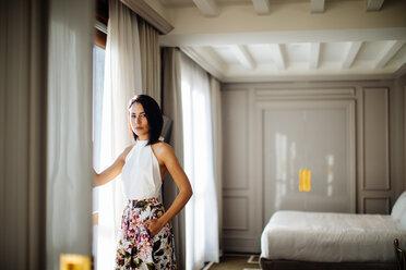 Fashionable woman beside window in suite - CUF48092