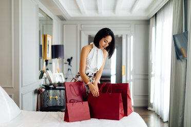 Fashionable woman with shopping bags in suite - CUF48095