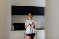 Young woman with mug in kitchen - CUF48101