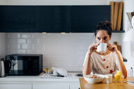 Young woman drinking coffee in kitchen - CUF48104