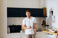 Young man using smartphone in kitchen - CUF48110