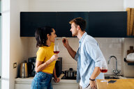 Young man feeding woman in kitchen - CUF48116