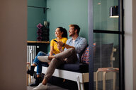 Young couple watching television on couch - CUF48119