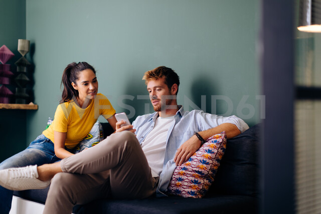 Young woman looking at man using smartphone on couch - CUF48122