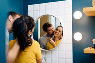 Young couple kissing in front of wall mirror in bathroom - CUF48125