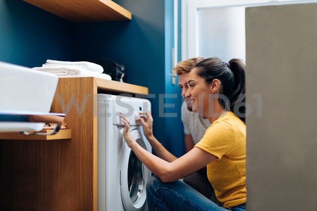 Young couple operating washing machine at home - CUF48128
