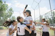 Enthusiastic middle school girl softball team celebrating on baseball diamond - HEROF05244