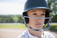 Close up portrait pensive middle school girl softball player wearing batting helmet - HEROF05247