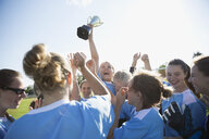 Exuberant middle school girl soccer team celebrating and cheering with trophy - HEROF05250