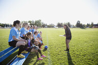 Coach preparing middle school girl soccer team on sunny field - HEROF05256