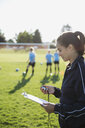 Coach with clipboard timing middle school girl soccer team running drills at practice on sunny field - HEROF05259