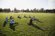 Coach and middle school girl soccer team stretching at practice on sunny field - HEROF05262