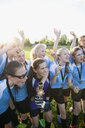 Exuberant middle school girl soccer team celebrating and cheering with trophy - HEROF05265