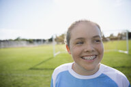 Close up smiling middle school girl soccer player with braces looking away on field - HEROF05268