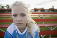 Close up portrait serious middle school girl soccer player listening to music with headphones on bleachers - HEROF05271