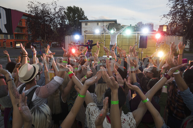 Crowd cheering musician on illuminated stage at summer music festival - HEROF05286