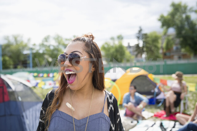 Enthusiastic young woman at summer music festival campsite - HEROF05289