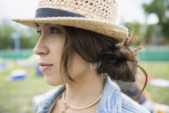 Close up portrait pensive young woman wearing straw hat looking away - HEROF05301