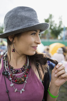 Close up portrait smiling young woman wearing hat looking away at summer music festival campsite - HEROF05307