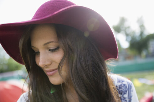 Close up portrait pensive young brunette woman in floppy hat looking down - HEROF05310