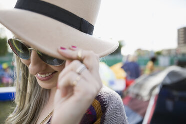 Close up portrait young woman wearing hat and sunglasses looking down at summer music festival campsite - HEROF05313