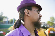 Close up portrait pensive young man with ponytail and beard wearing purple hat looking away - HEROF05322