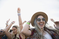Enthusiastic young woman dancing in crowd at summer music festival - HEROF05331