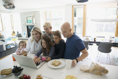 Family in pajamas using digital tablet in morning kitchen - HEROF05349
