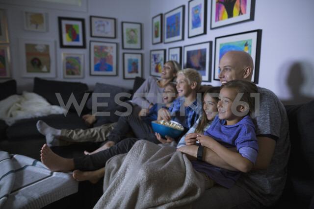 Family eating popcorn watching movie in dark living room - HEROF05355