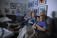 Family eating popcorn watching movie in dark living room - HEROF05355
