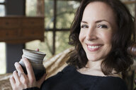 Close up portrait smiling mature brunette woman drinking coffee - HEROF05364