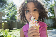 Close up portrait girl eating ice cream cone with sprinkles in sunny backyard - HEROF05367