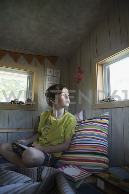Curious boy with digital tablet looking out window - HEROF05376